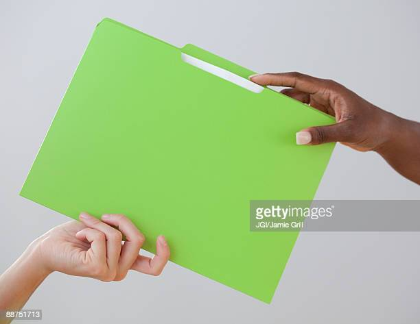 african woman handing co-worker a folder - delegating stock photos and pictures