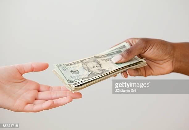 African woman handing over stack of 20 dollar bills