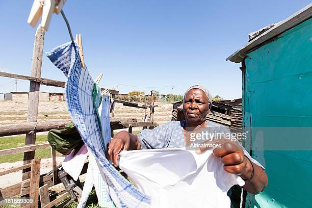 african woman hanging up laundry - gugulethu stock pictures, royalty-free photos & images
