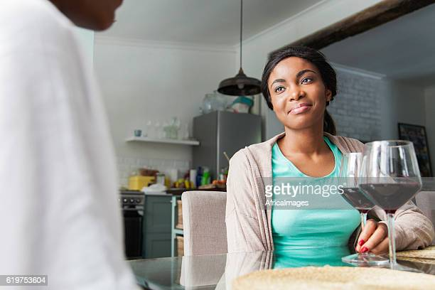 African woman having a glass of wine together.