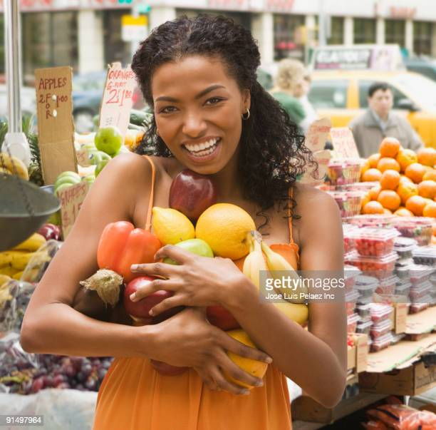 African woman holding armful of fruits and vegetables