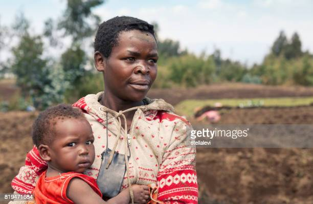african woman holding baby, rwanda - rwanda stock pictures, royalty-free photos & images