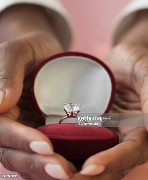 African woman holding engagement ring in box
