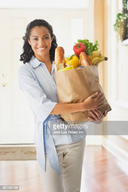 African woman holding grocery bag