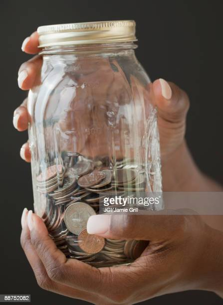african woman holding jar of coins - 40 44 jaar stock pictures, royalty-free photos & images