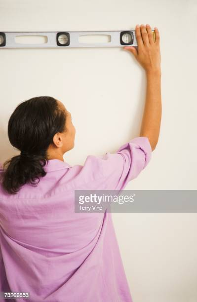 African woman holding level on wall