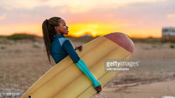 prancha africana da terra arrendada da mulher e passeio na praia no por do sol - aventura - fotografias e filmes do acervo