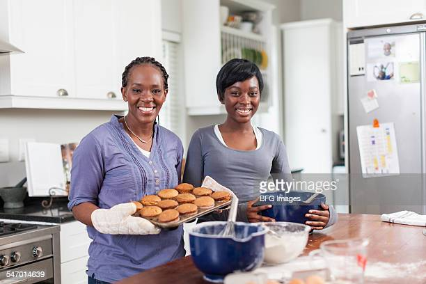 African woman holding tray of freshly baked cupcakes with teenaged daughter next to her  , Cape Town, South Africa