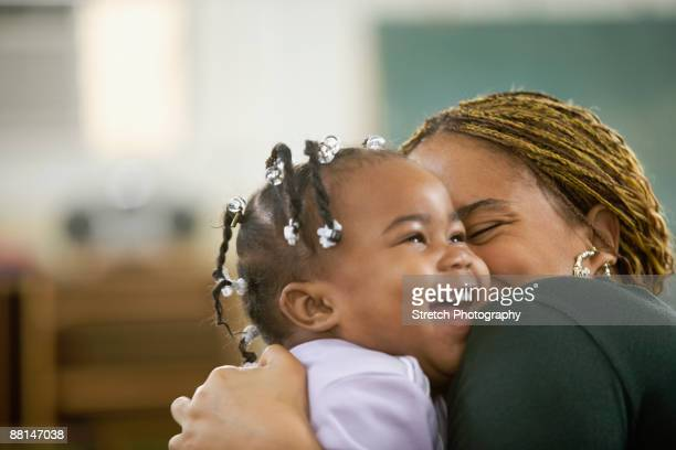 African woman hugging daughter