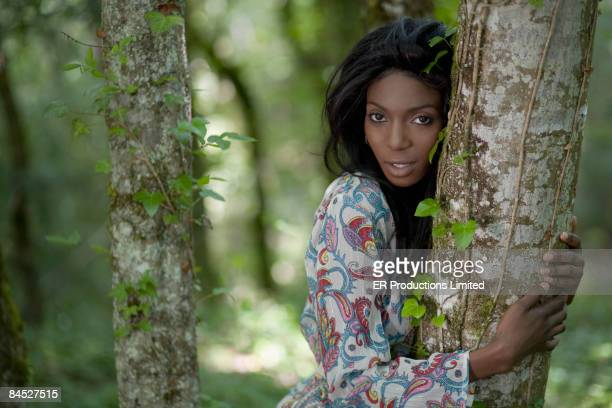 African woman hugging tree trunk