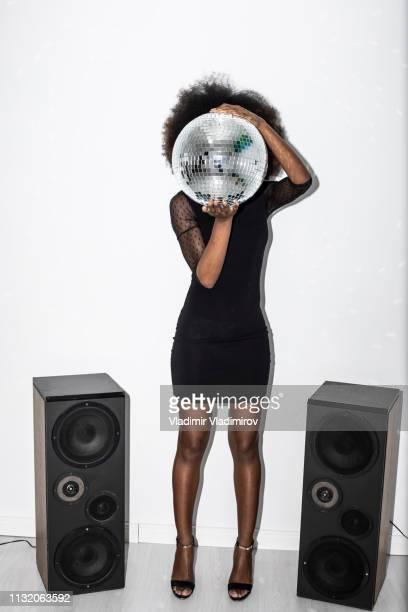 黒いドレスのアフリカの女性はディスコボールを保持し、隠す - funny black girl ストックフォトと画像