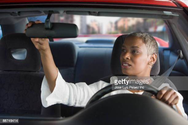 African woman in car adjusting mirror