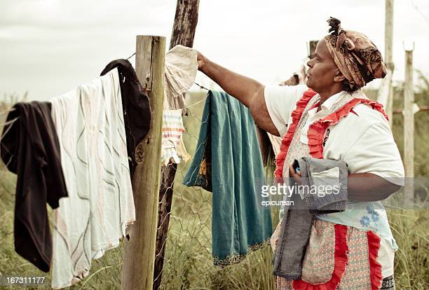 African woman in traditional dress hanging laundry