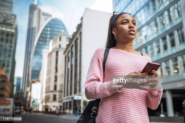African woman in UK, using mobile app or GPS device.