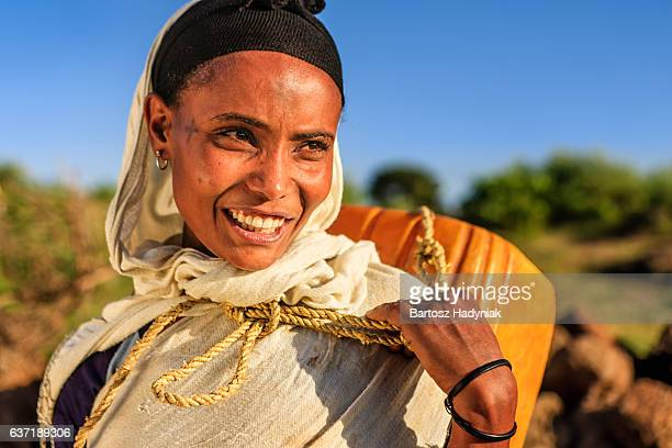 African woman is carring water to her house, Ethiopia, Africa