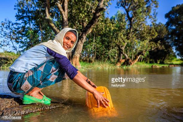 african woman is taking water from the river, ethiopia, africa - ethiopia stock pictures, royalty-free photos & images
