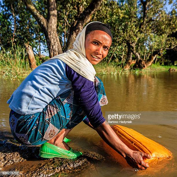 African woman is taking water from the river, Ethiopia, Africa