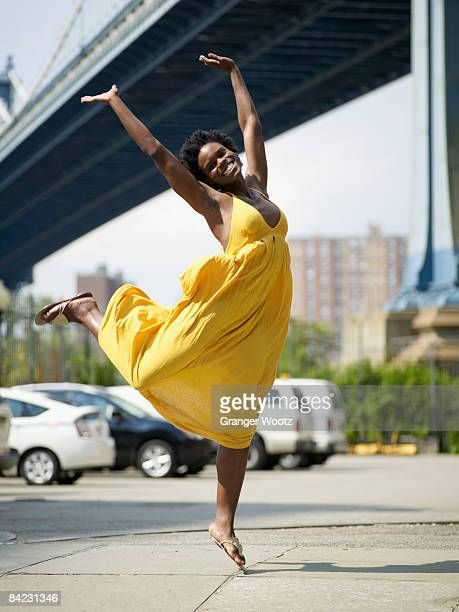 African woman jumping in mid-air in urban setting