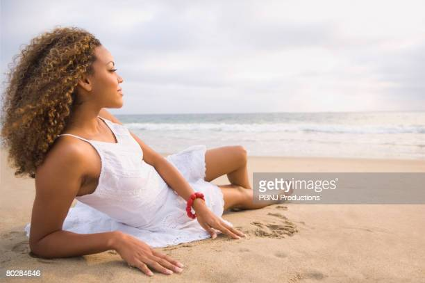 African woman laying on sand