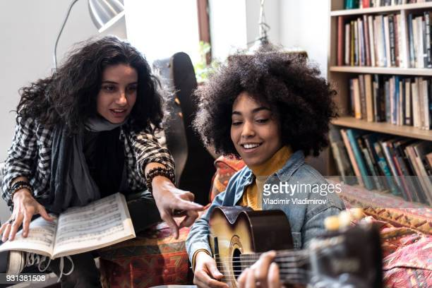 African woman learning playing a guitar with teacher