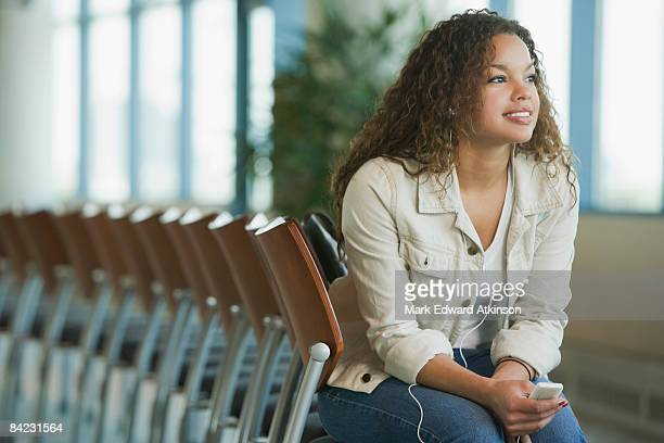 African woman listening to mp3 player waiting in airport