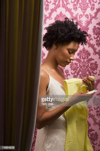 African woman looking at price tag on dress in fitting room