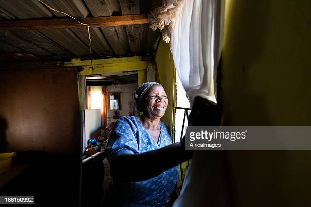 african woman looking out her window - gugulethu stock pictures, royalty-free photos & images