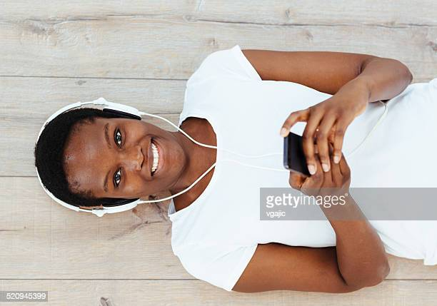 African Woman Lying and Typing on Smart Phone.