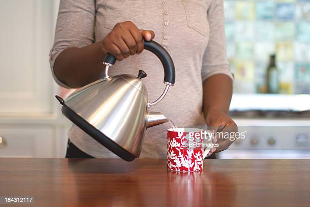 african woman making tea, cape town, south africa - red kettle stock photos and pictures