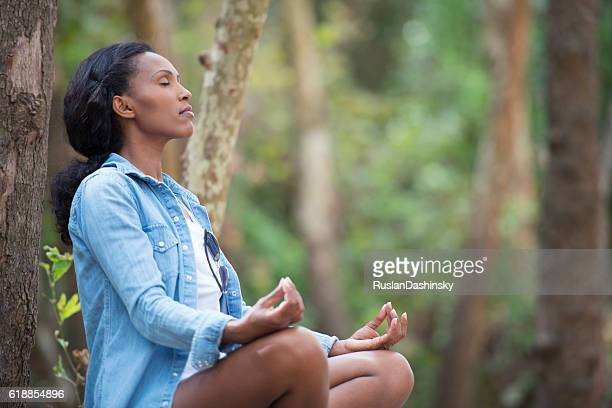 African woman meditating in forest.