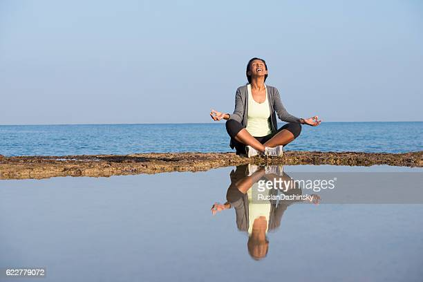 African woman meditating on seashore.