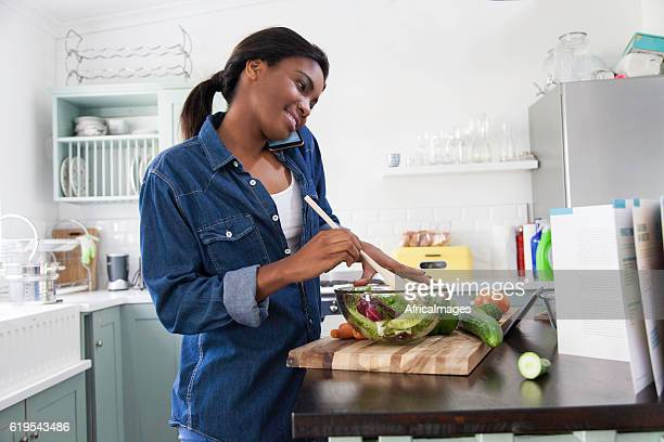 African woman on the phone while preparing lunch.