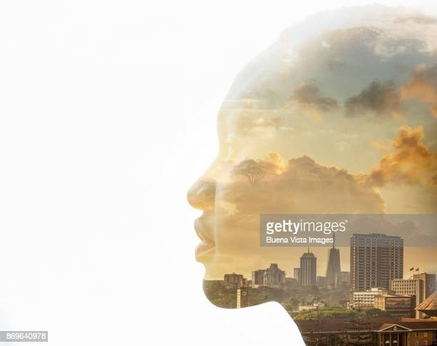African woman over sunset and city skyline