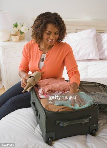 African woman packing suitcase
