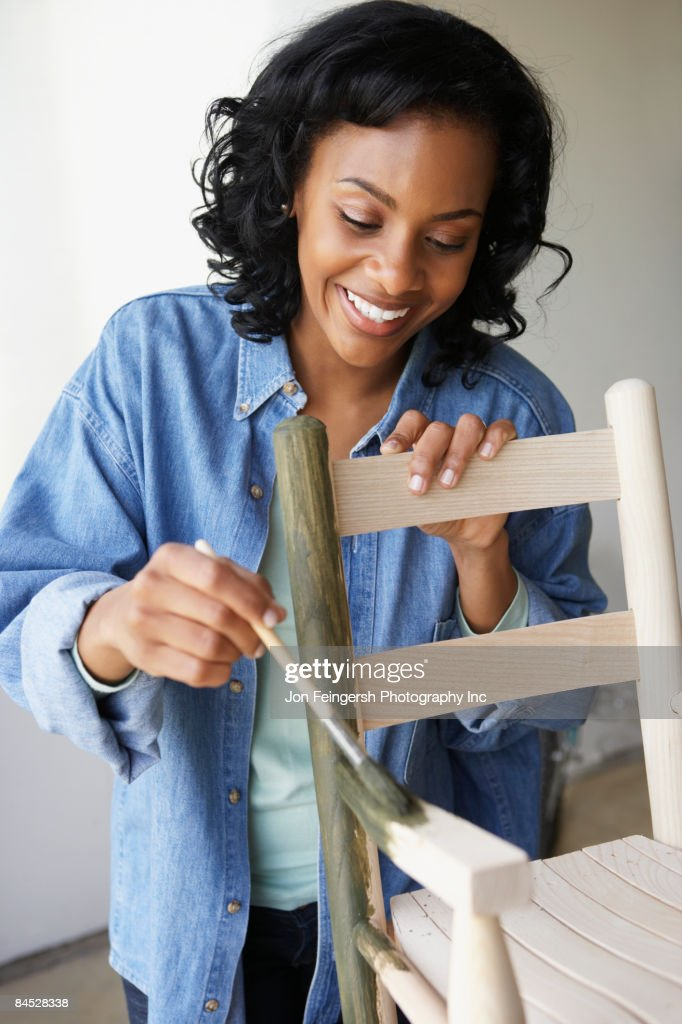 African woman painting rocking chair : Stock Photo