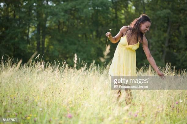 African woman picking flowers in field