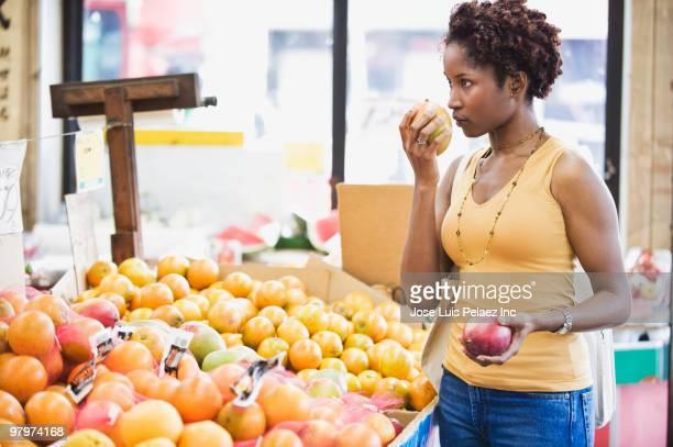 African woman picking fruit in market