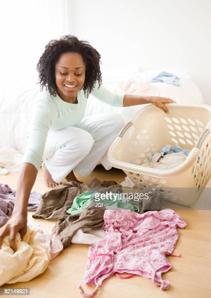 African woman picking up dirty laundry