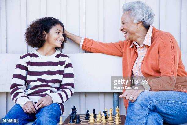 African woman playing chess with granddaughter