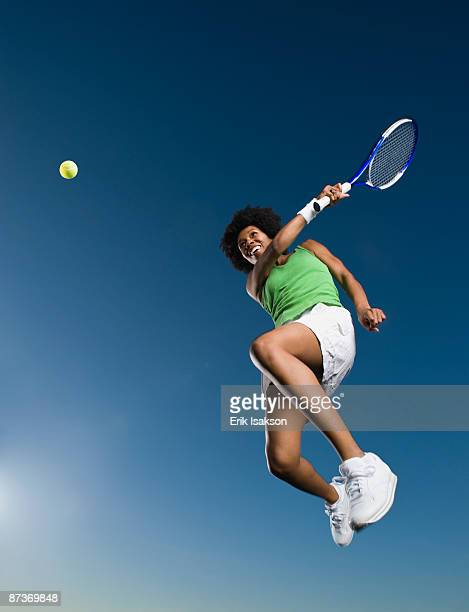 African woman playing tennis in mid-air