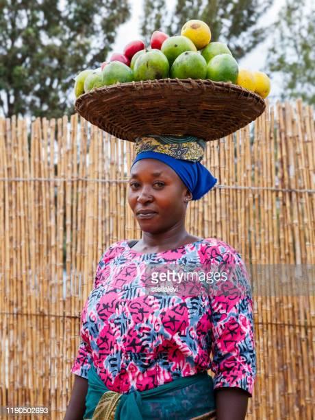 彼女の頭にフルーツとバスケットを運ぶアフリカの女性の肖像画、ルワンダ - キガリ ストックフォトと画像