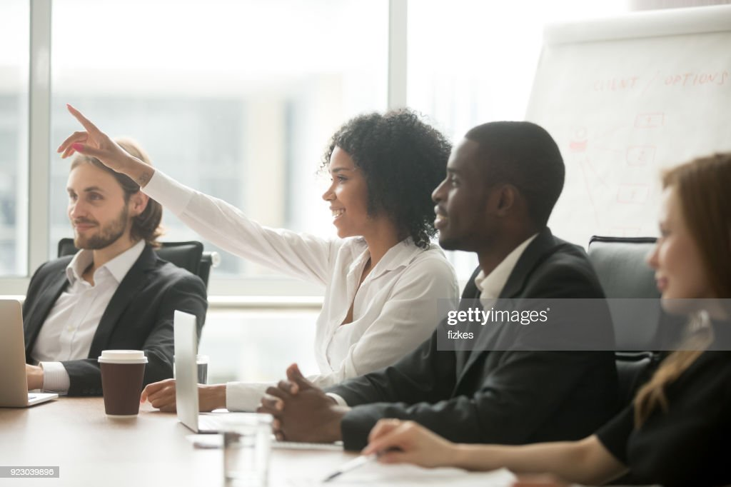 African woman raising hand to ask question at team training : Foto de stock
