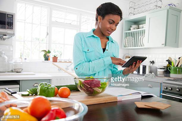 African woman reading a recipe.