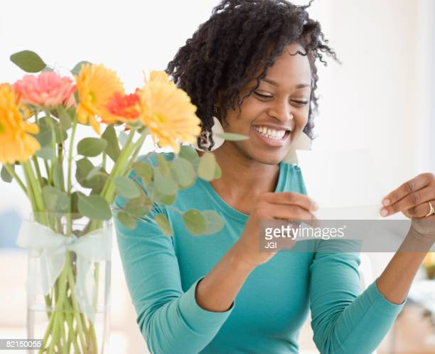 African woman reading card next to flowers