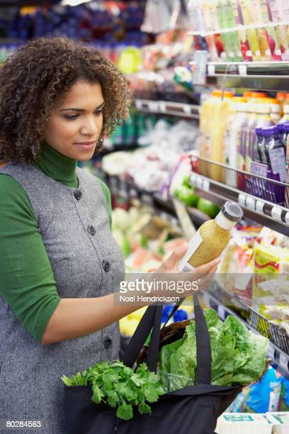 African woman reading label at grocery store