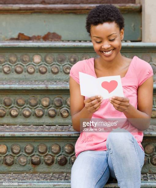 african woman reading valentine's day card - valentine card stock pictures, royalty-free photos & images