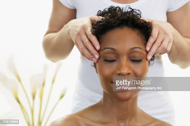 african woman receiving facial massage - head massage stock photos and pictures