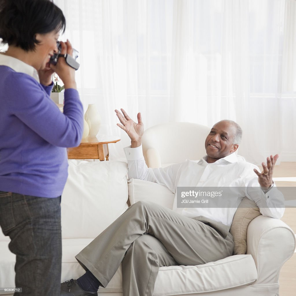 African woman recording husband in livingroom : Stock Photo
