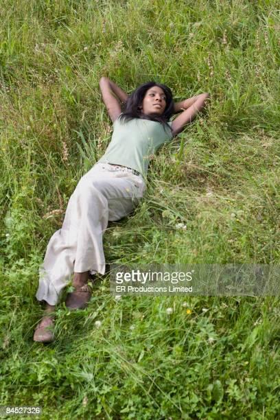 African woman relaxing in grass