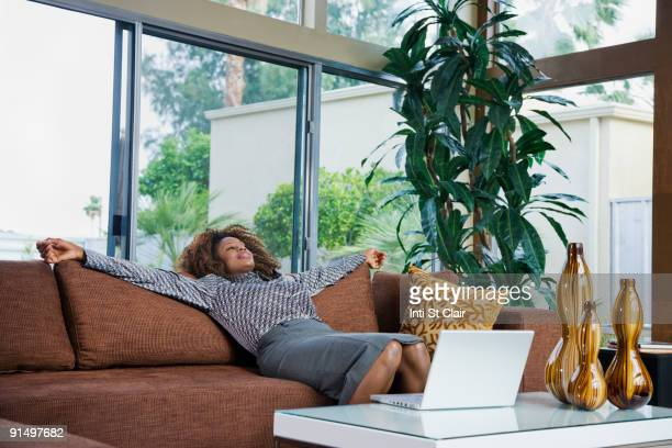 African woman relaxing on sofa in modern living room